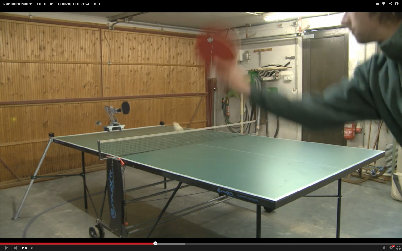 camera in the upper right of the garage door is in front of the table tennis racket